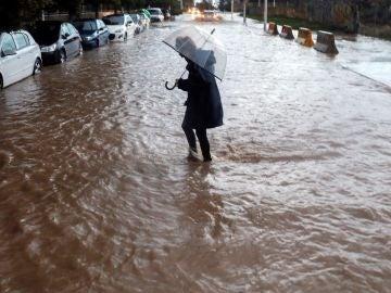 Una persona cruza una calle inundada durante el temporal en Valencia