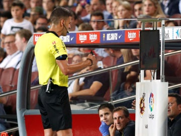 El árbitro Gil Manzano consulta el VAR durante el Clásico