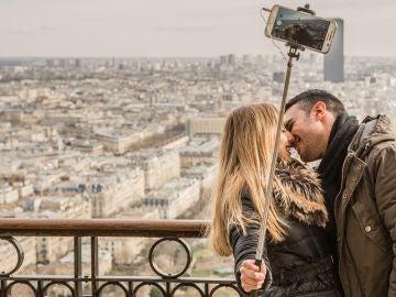 Pareja besándose mientras se hace un selfie