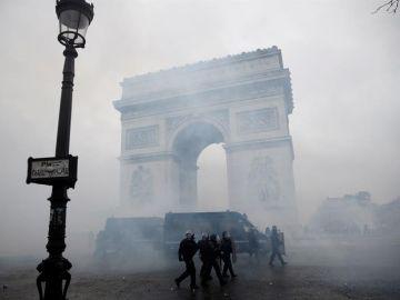 La policía francesa pasa ante el Arco del Triunfo tras los disturbios en París
