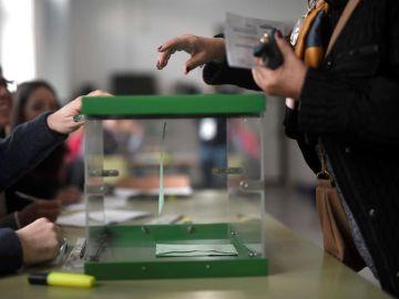Una mujer deposita su voto en el colegio Colón en Córdoba