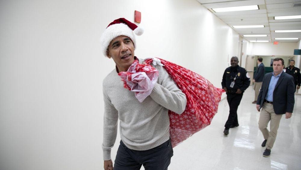 El expresidente de EEUU Barack Obama entrega regalos en un hospital para niños en Washington.