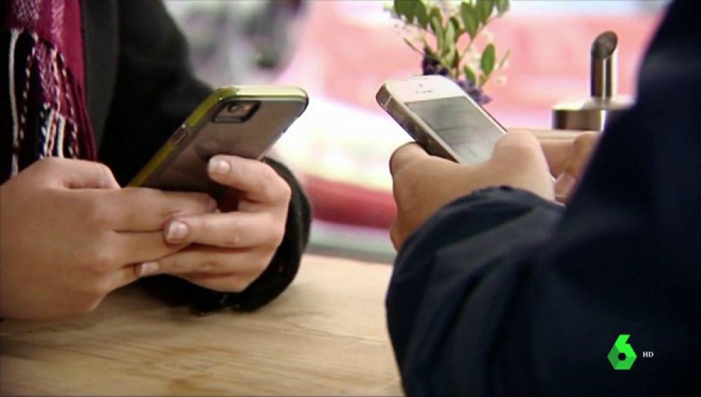 Dos personas con sus móviles