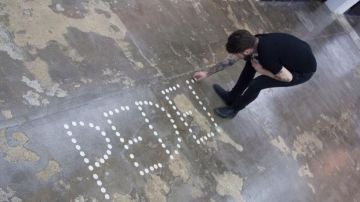 "Abel Azcona dibujando con hostias la palabra ""pederastia"""