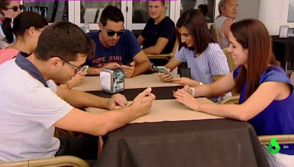 Un grupo de personas alrededor de una mesa mirando el móvil