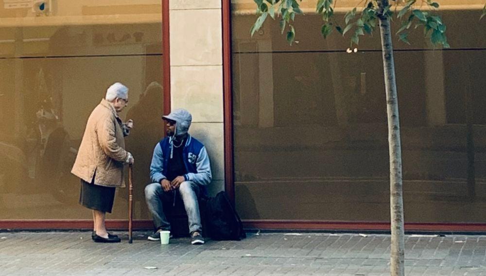 Mercedes, una monja de 86 años, charlando con Osakpamwan, un hombre nigeriano de 43 años