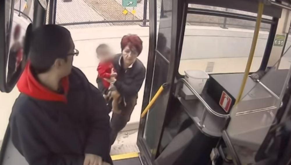 La conductora metiendo al pequeño en el autobús