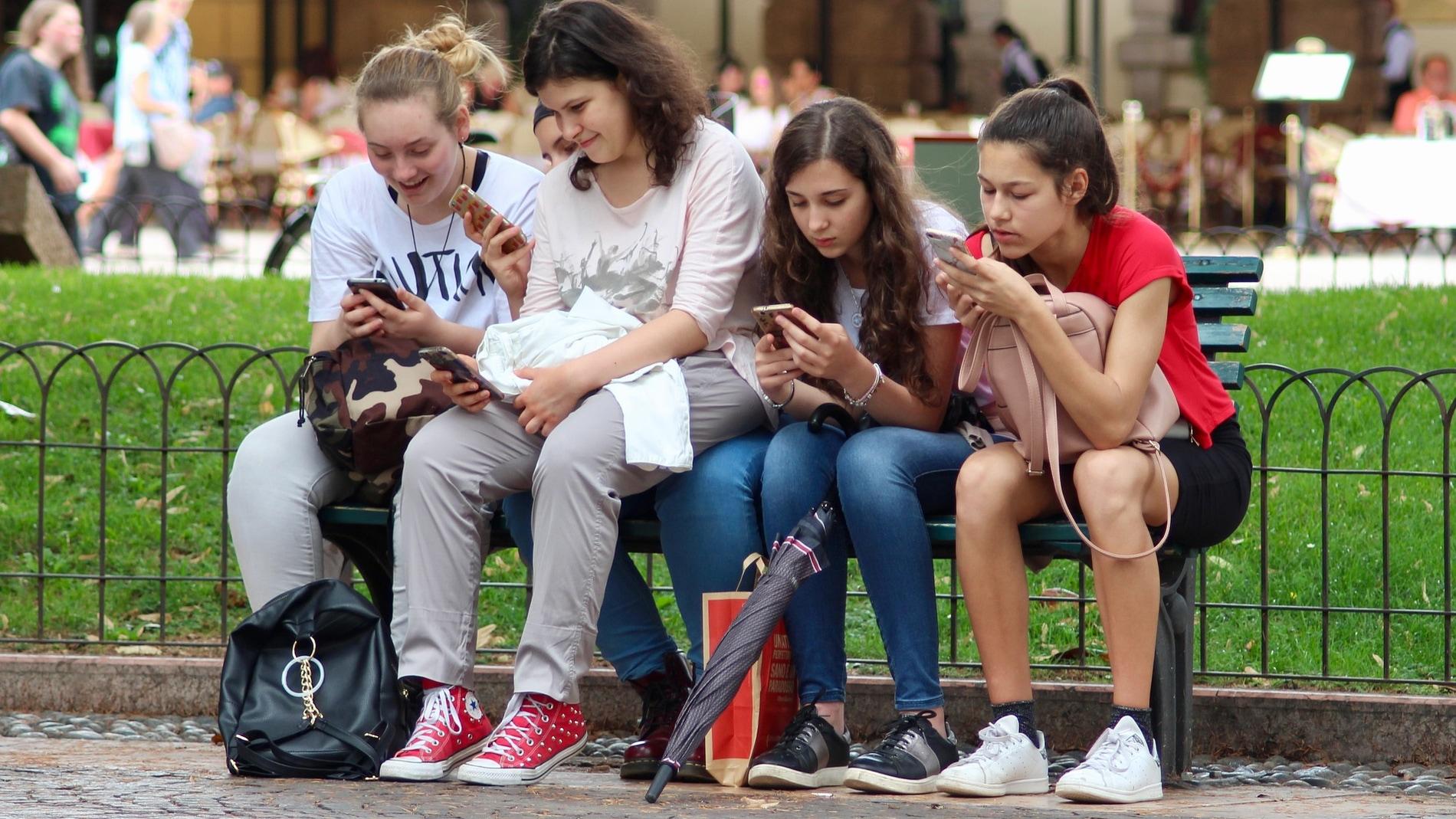 Jóvenes consultando sus móviles.