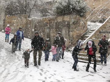 Adultos y niños caminan bajo una intensa nevada caída sobre Damasco.