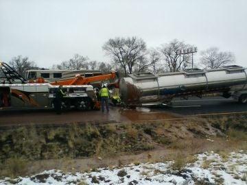 Un camión grúa intenta remolcar la cisterna de un camión.