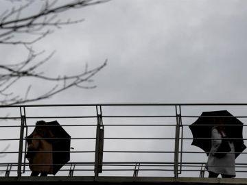 Imagen de archivo: varias personas se protegen del agua y del viento.