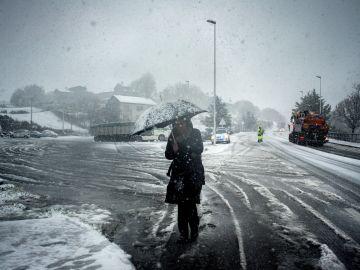 Una mujer se protege de la nevada este viernes en A Gudina (Ourense)