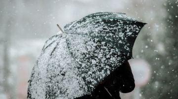 Una mujer camina por una calle nevada en A Gudiña
