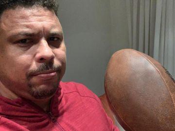 Ronaldo Nazario posa con un balón de fútbol americano