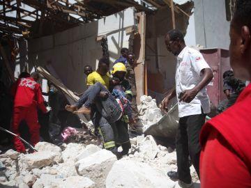 Un bombero somalí retira el cadáver de una víctima tras la explosión en Mogadiscio