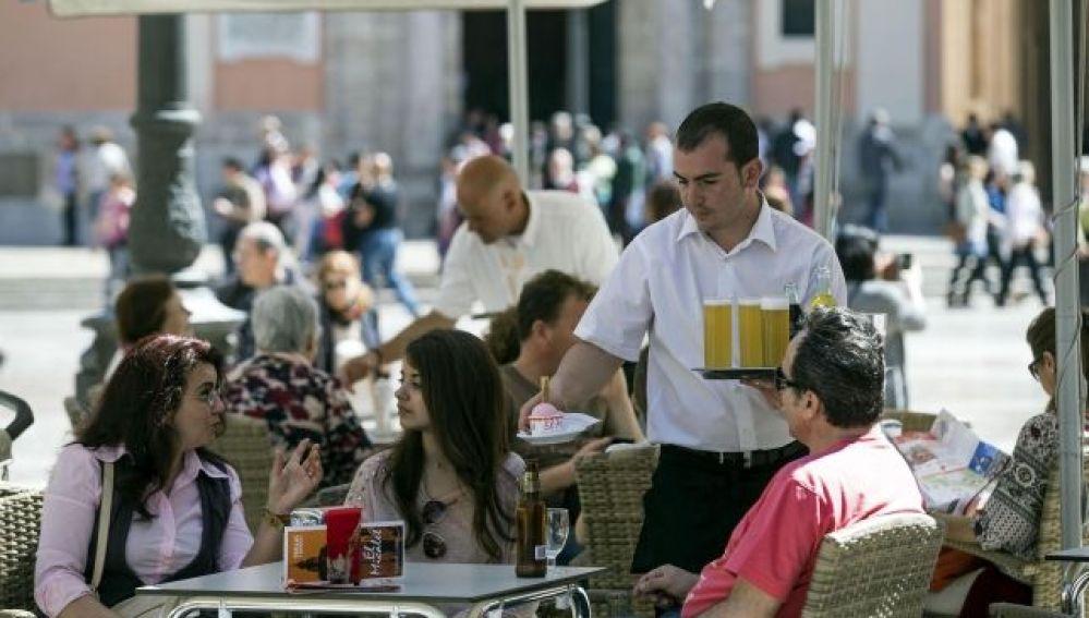 Un camarero atiende la mesa de una terraza.