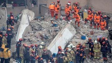 Miembros de los servicios de rescate trabajan entre los escombros del edificio de ocho plantas derrumbado en Estambul