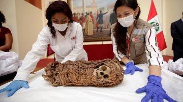 Dos mujeres junto a una momia de un niño de origen aimara