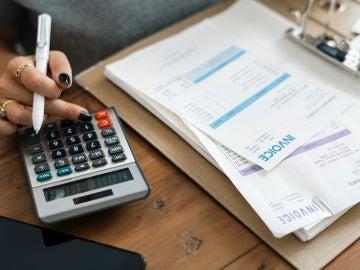 Una mujer revisa sus facturas con la ayuda de una calculadora