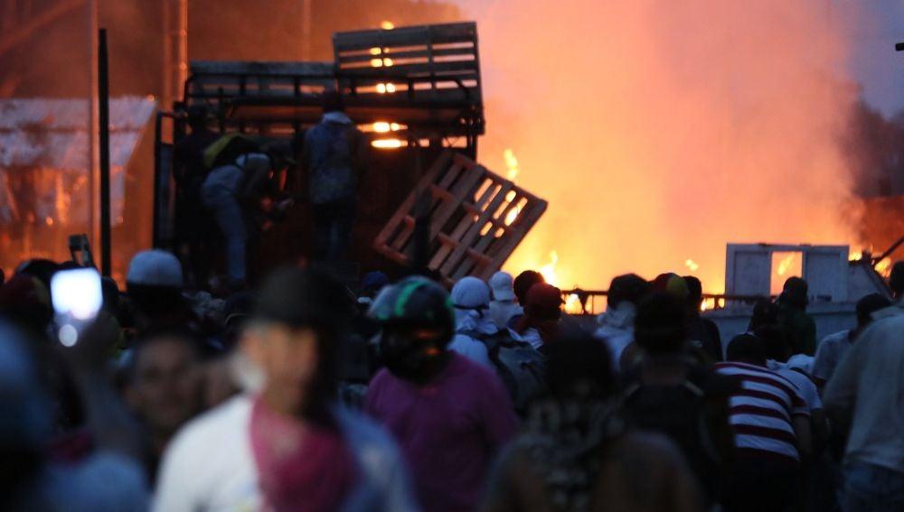Manifestantes se enfrentan con miembros de la Policía Nacional Bolivariana, junto a un camión que transportaba ayuda humanitaria y fue quemado.