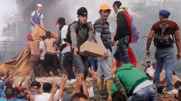 Personas intentan sacar parte de la ayuda humanitaria que se encuentra un camión que fue quemado
