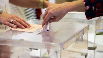 Una mujer deposita su voto en una urna electoral