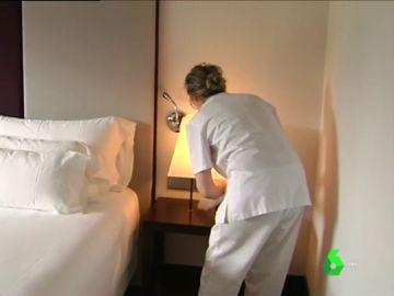 Una mujer limpia la habitación de un hotel