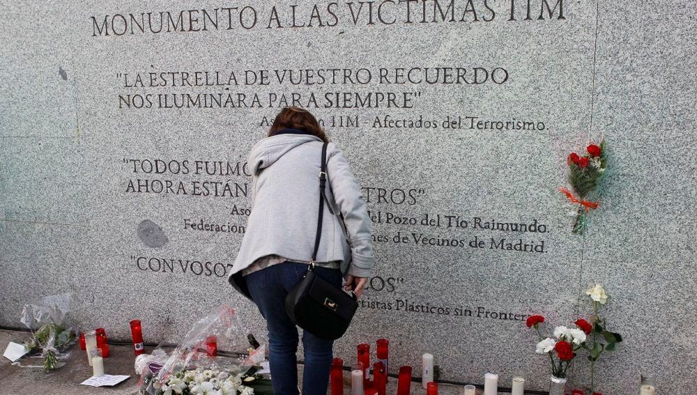Flores y velas junto al monumento a las víctimas de los atentados del 11M