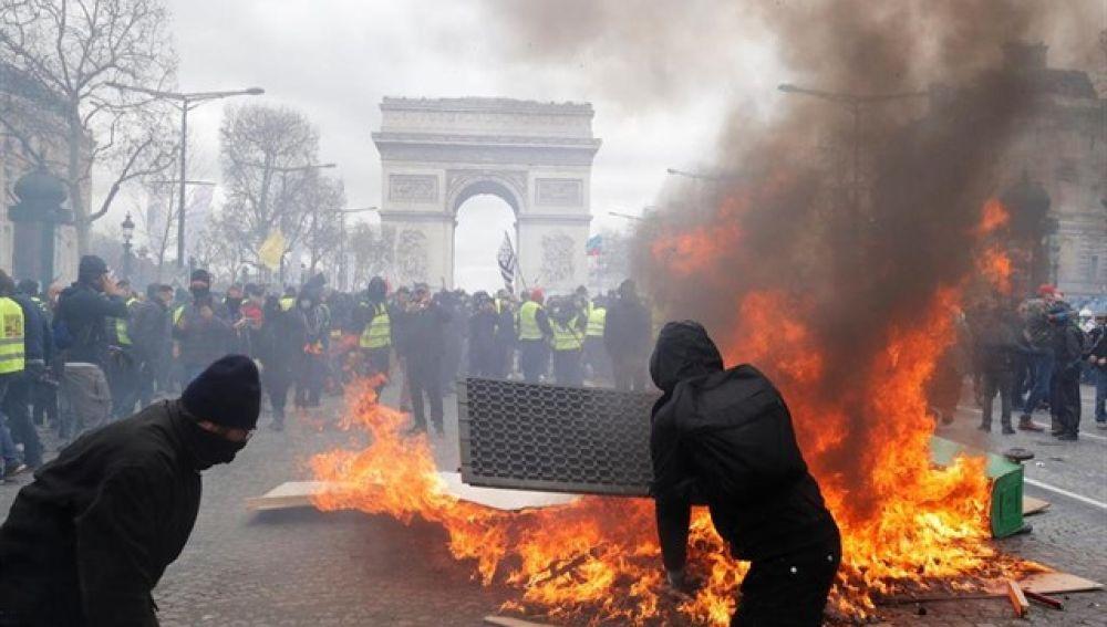 Manifestantes de los 'chalecos amarillos' queman contenedores en París