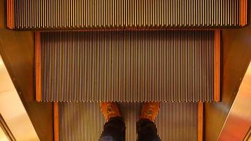 Tú mirando al suelo mientras decides si esperar de pie o caminar en la escalera mecánica