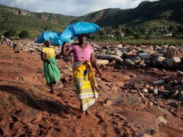 Dos mujeres portan sacos con ayuda humanitaria destinados a los afectados por el ciclón Idai