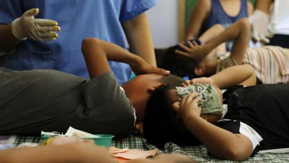 Jóvenes filipinos muestran dolor mientras les practican una circuncisión