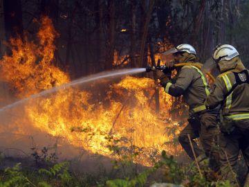 Bomberos apagan uno de los numerosos focos del incendio en la localidad coruñesa de Rianxo