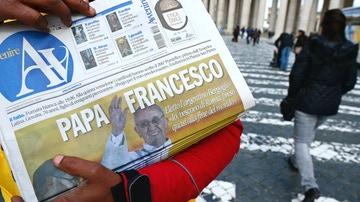 Una persona sostiene un periódico con Francisco en portada tras ser elegido papa.