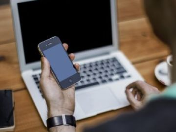 Un hombre sostiene un smartphone frente a un ordenador portátil.