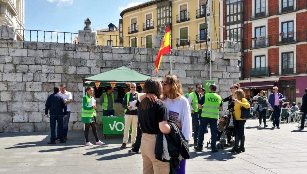 Una pareja de lesbianas se besa frente a un puesto de Vox