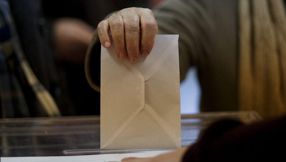 Una persona introduce un sobre en una urna electoral.