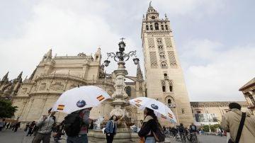 Turistas pasean por las inmediaciones de la Torre de la Giralda de Sevilla