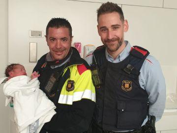 Los dos agentes de los Mossos d'Esquadra junto al recién nacido en el hospital.