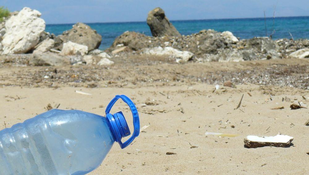 Una botella de plástico junto con otros residuos en una playa