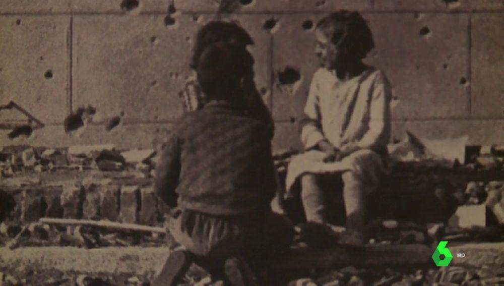 Niños sobre una pared con impactos de Metralla