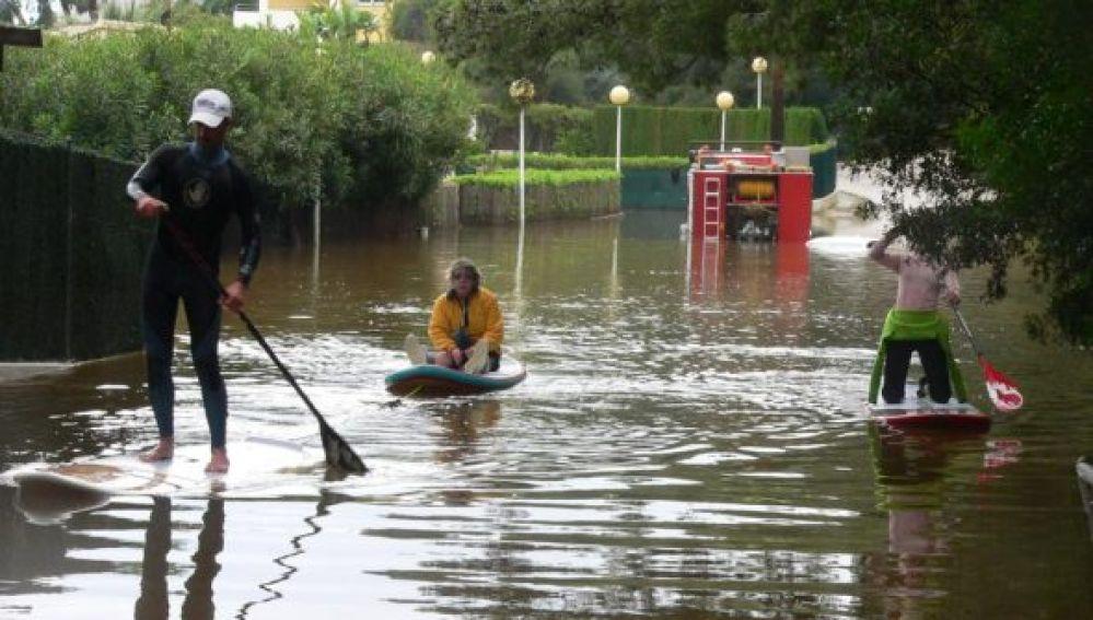 Jacinta es rescatada por sus vecinos subida a una tabla de paddle surf.