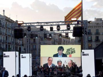 Carles Puigdemont desde Bruselas, y Josep Rull (i) Jordi Sánchez (c) y Jordi Rull (d), desde Soto del Real, intervienen en le acto de final de campaña de JxCat en Barcelona.