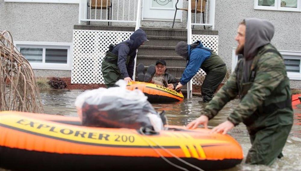 Personas siendo evacuadas en lancha tras las inundaciones en Quebec