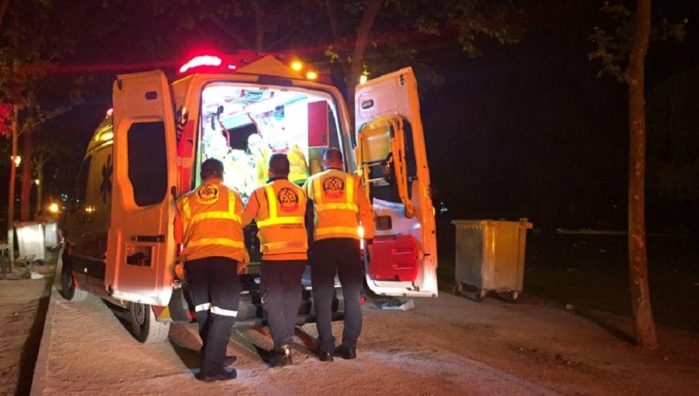 Una ambulancia con efectivos atendiendo al joven herido en una reyerta en Madrid