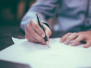 Un hombre escribe en un papel