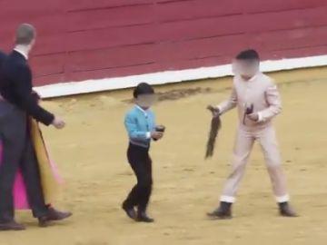 Varios niños participan en una corrida de toros de Córdoba: lucen las orejas que acaban de cortar al animal vivo