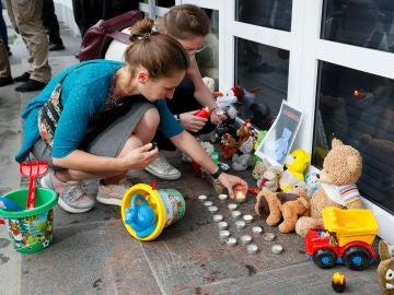 Manifestantes ponen velas durante una protesta por la muerte del niño