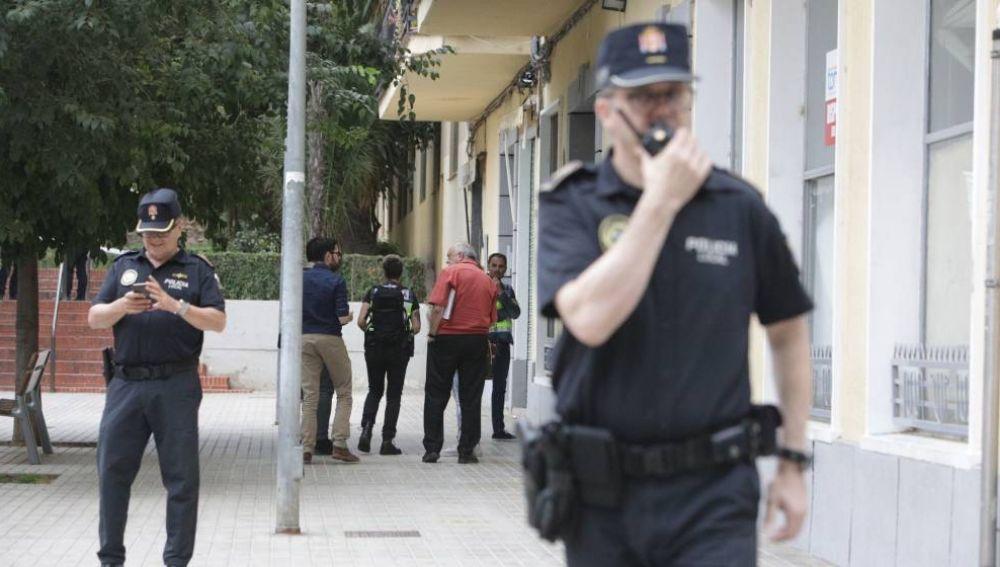 Agentes de Policía frente a la vivienda de la mujer hallada muerta en Xátiva