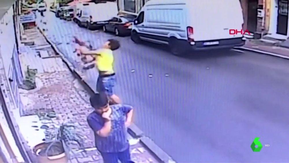 Un joven migrante coge al vuelo a una bebé que acababa de caerse por la ventana